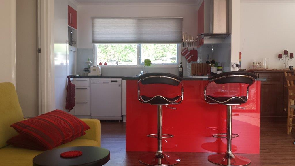 Red and white color theme kitchen with stylish breakfast counter and chairs.