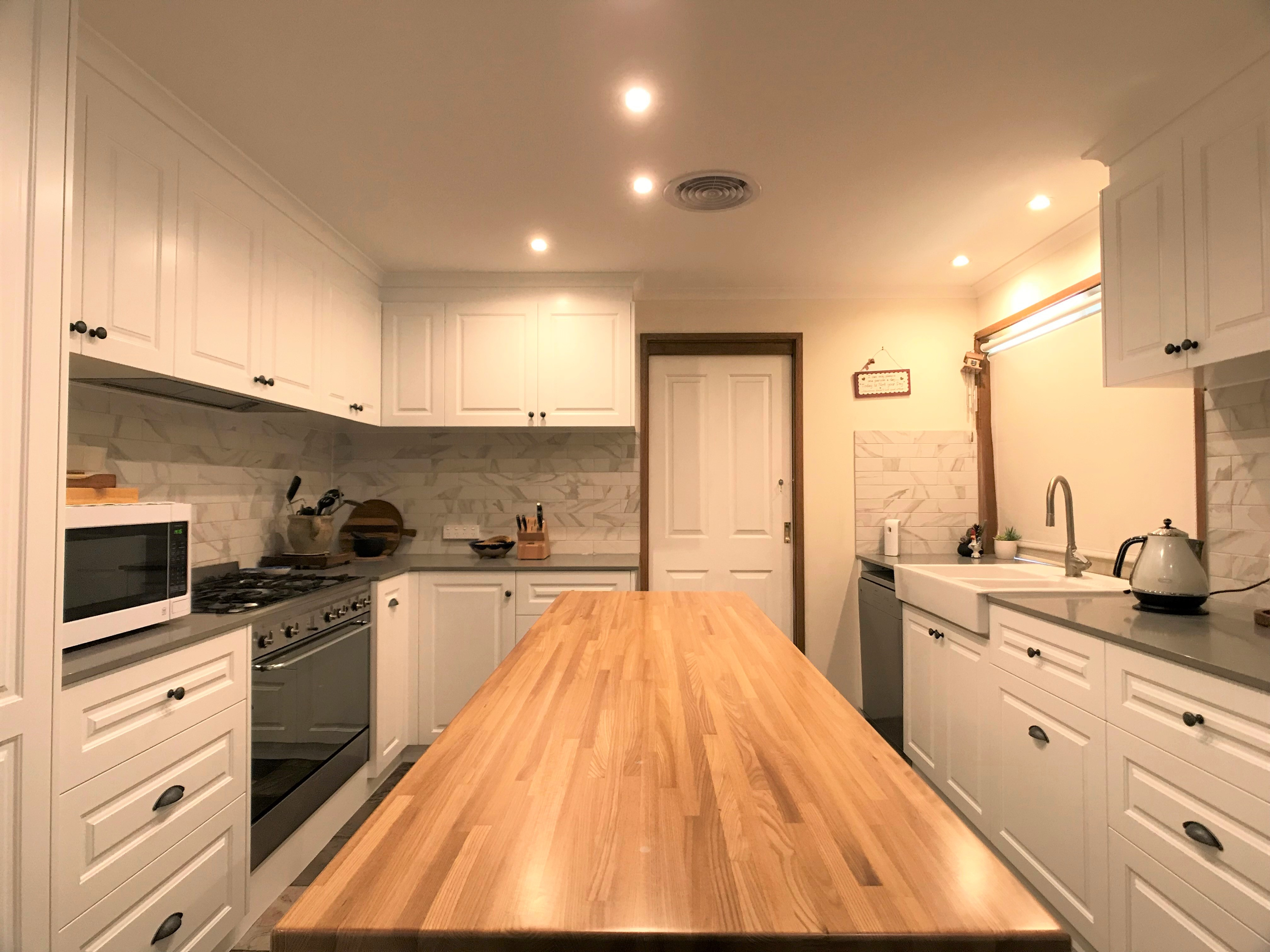 Kitchen with white walls,shelves and timber benchtop at the center.