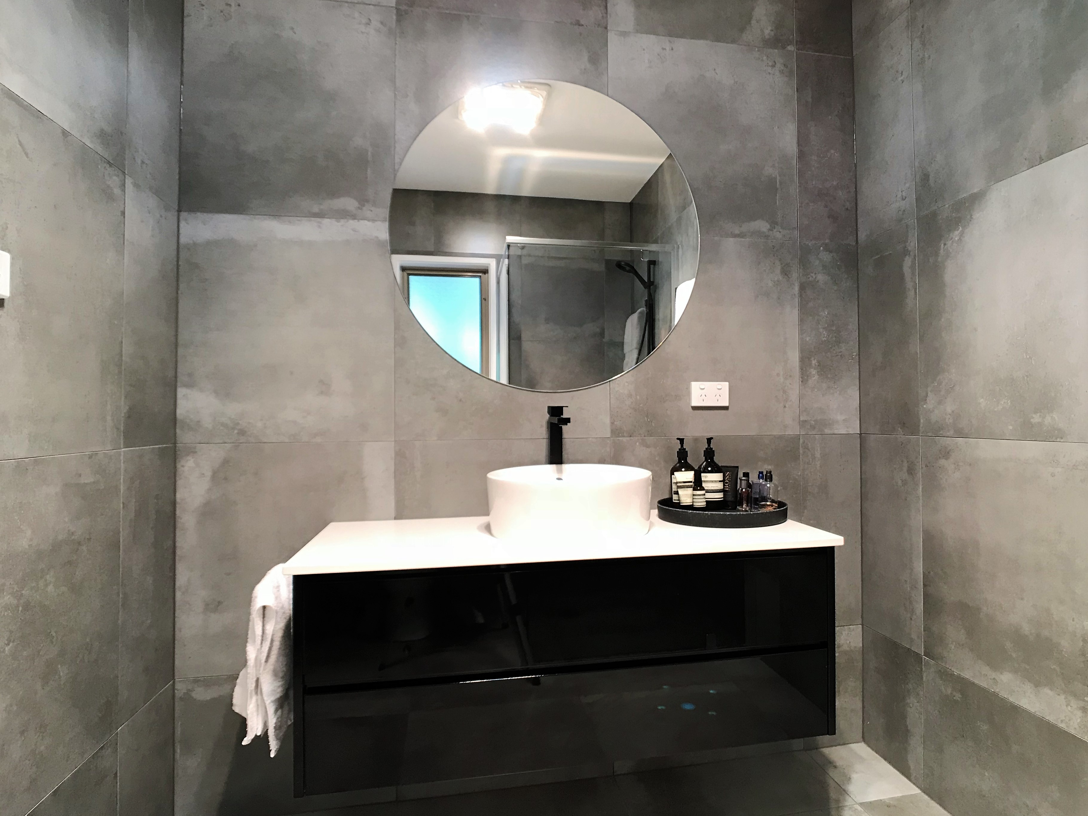 Stylish bathroom with round mirror and stylish amenities. - Bathroom Renovation
