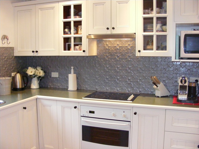 Kitchen with white drawers,shelves,oven.