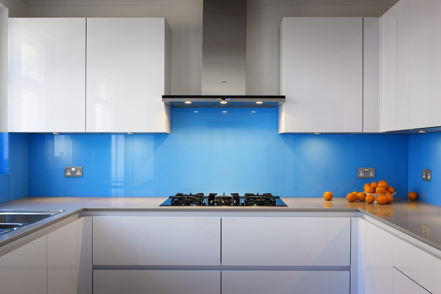 Kitchen with white shelves,drawers,benchtop and blue wall.