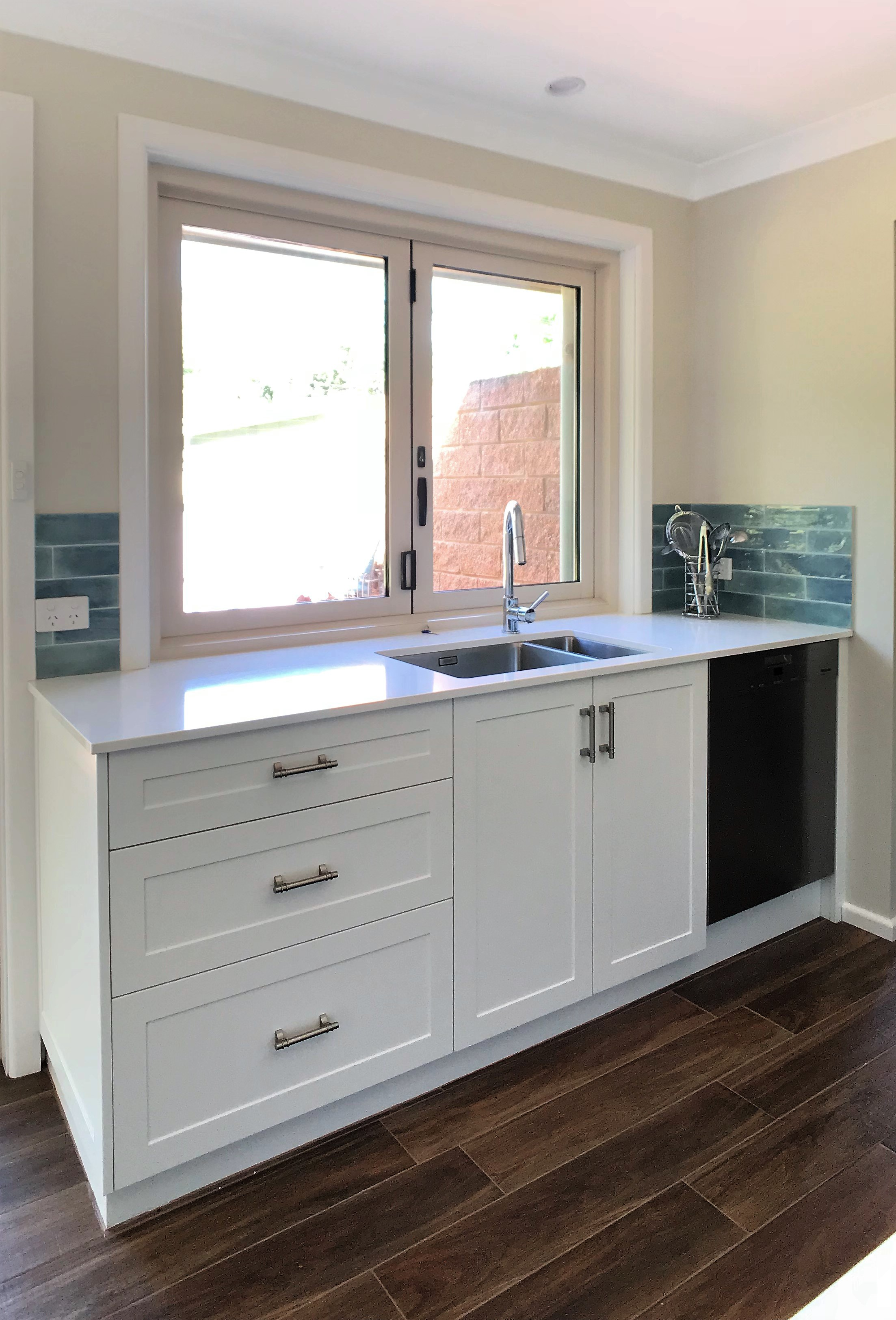 White color benchtop with sink for washing utensils.