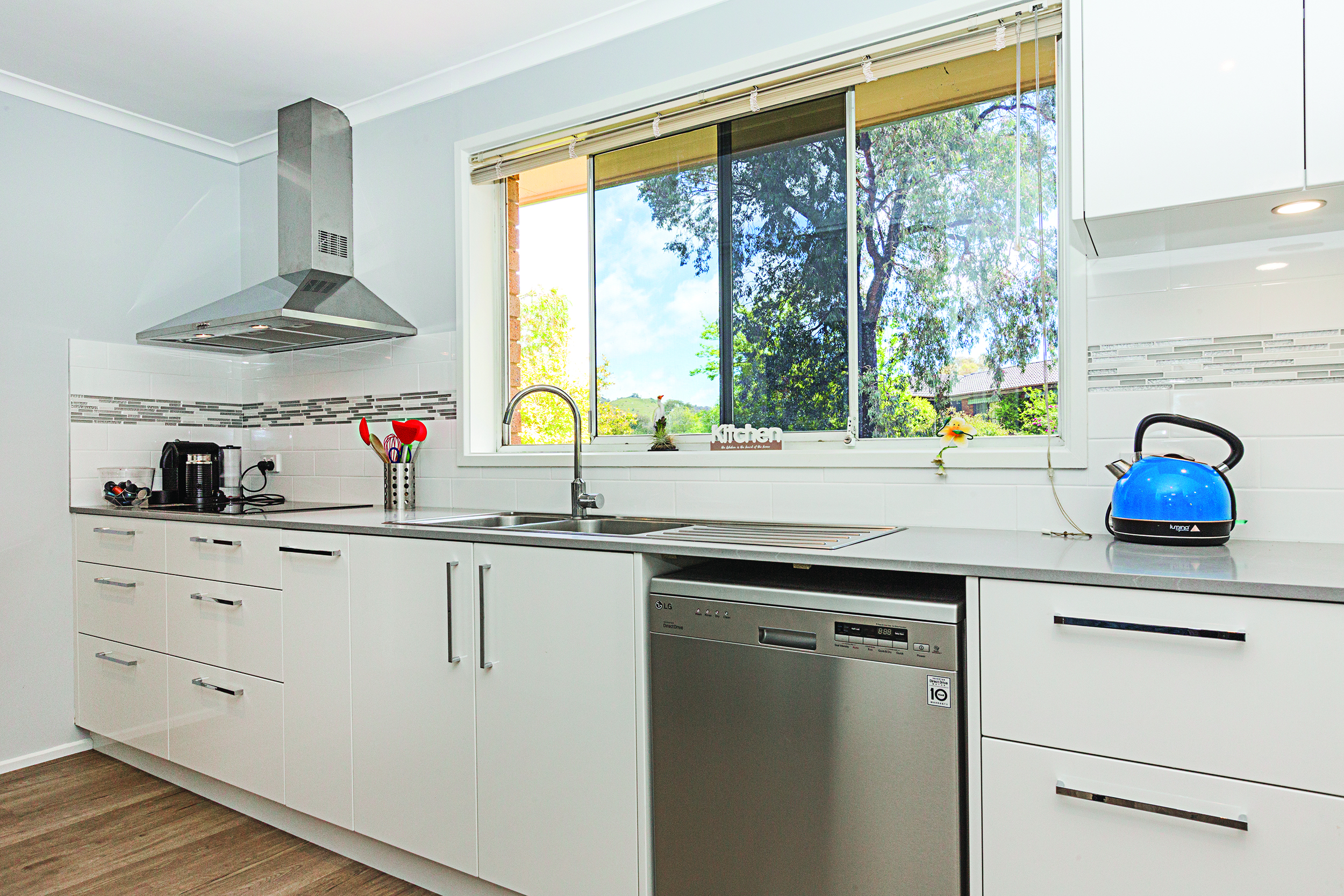Modular kitchen with white color walls,countertops,shelves.