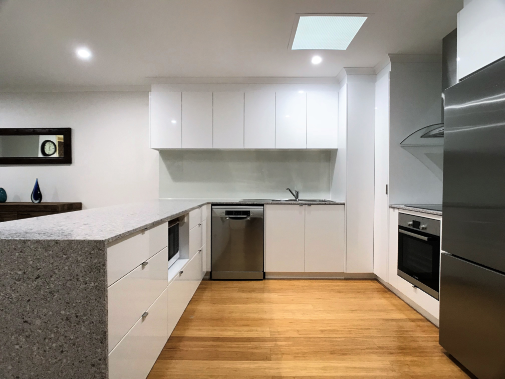 Paramount Creations renovated kitchen with white shelves,stone benchtop,stylish sink,oven and fridge.