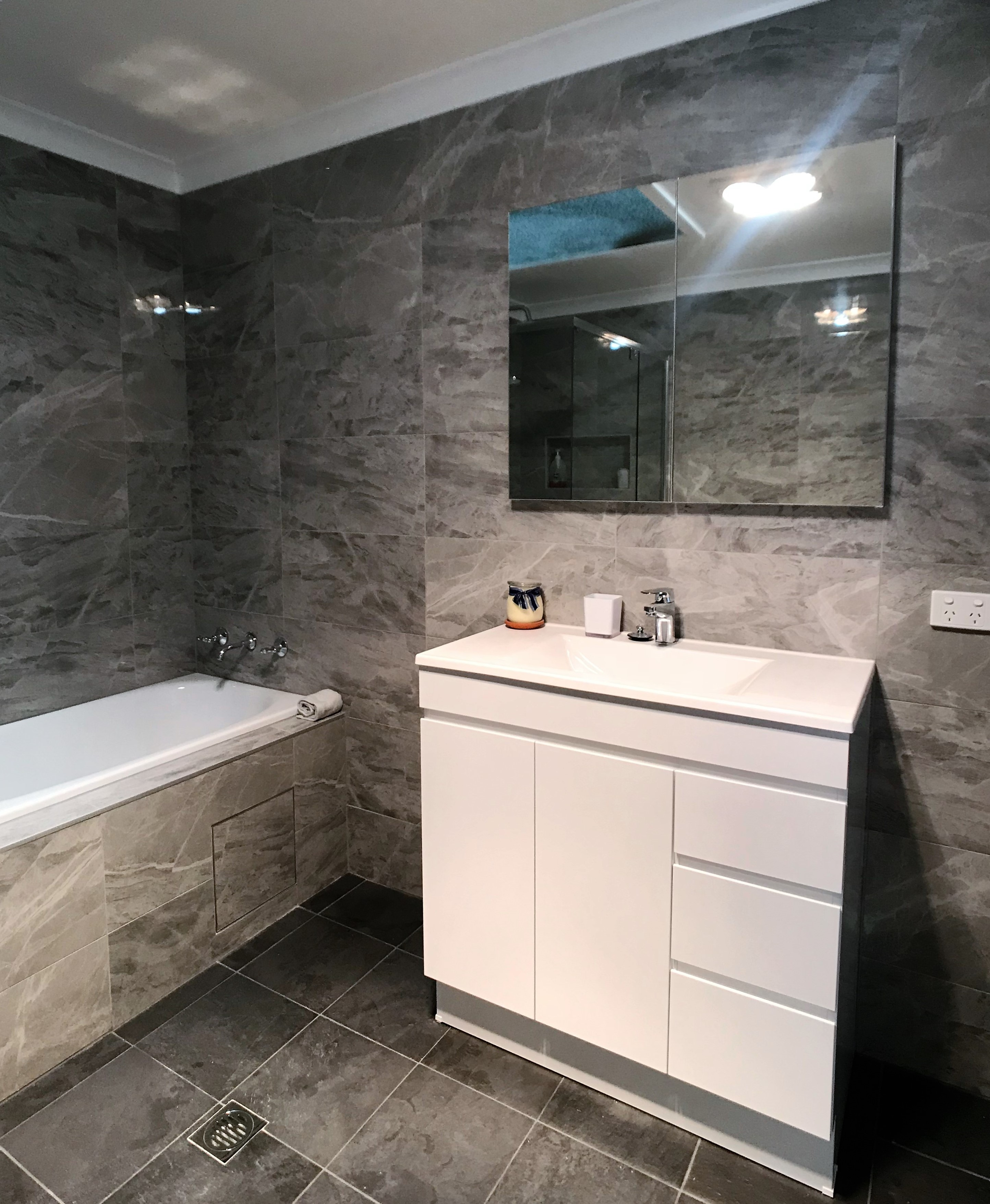 Bathroom with grey color tiles on walls and floors with white bathtub and countertops.