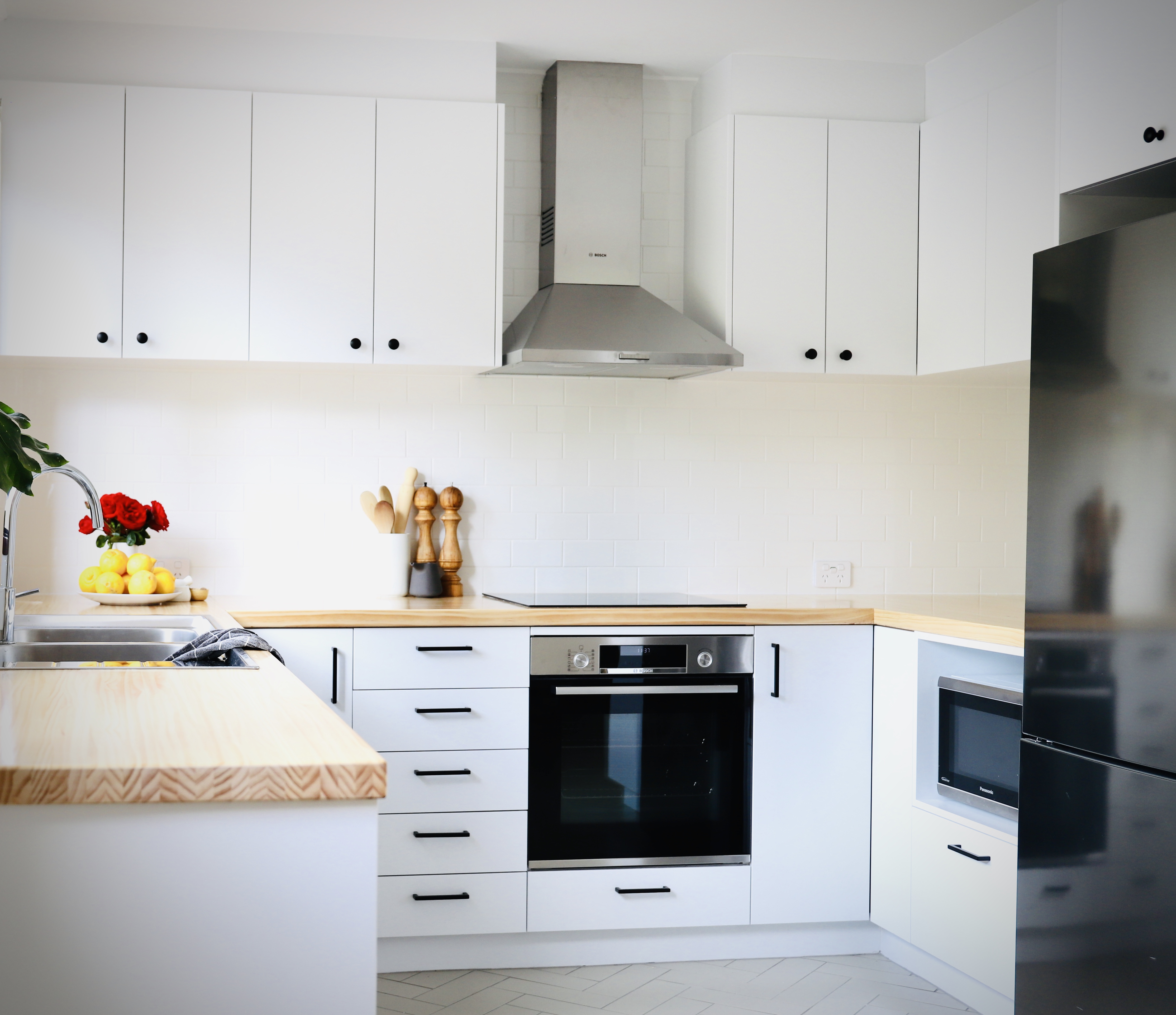 Modular kitchen with white cabinets, white shelves and wooden shade benchtops.